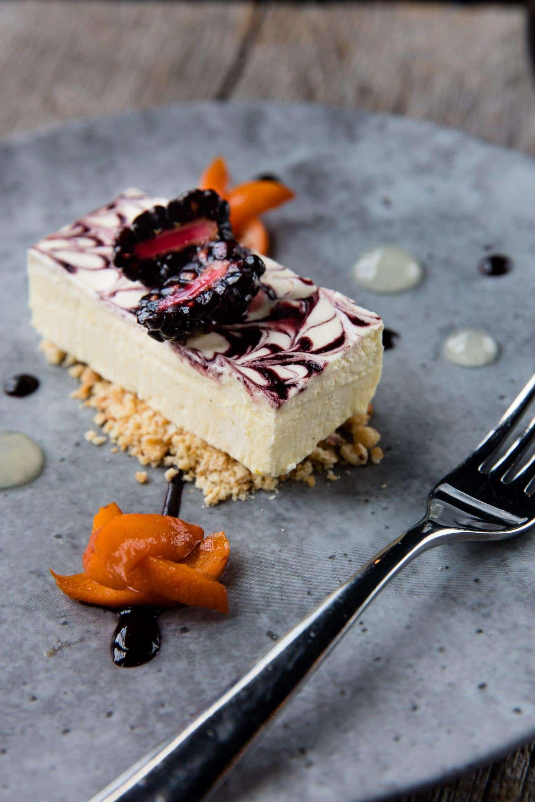 Dessert photographer Brent Herrig captured this rectangular slice of blackberry swirled cheesecake. It sits upon a grey plate.