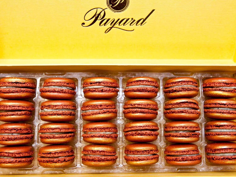 A yellow box of orange macaroons bears the Payard logo.