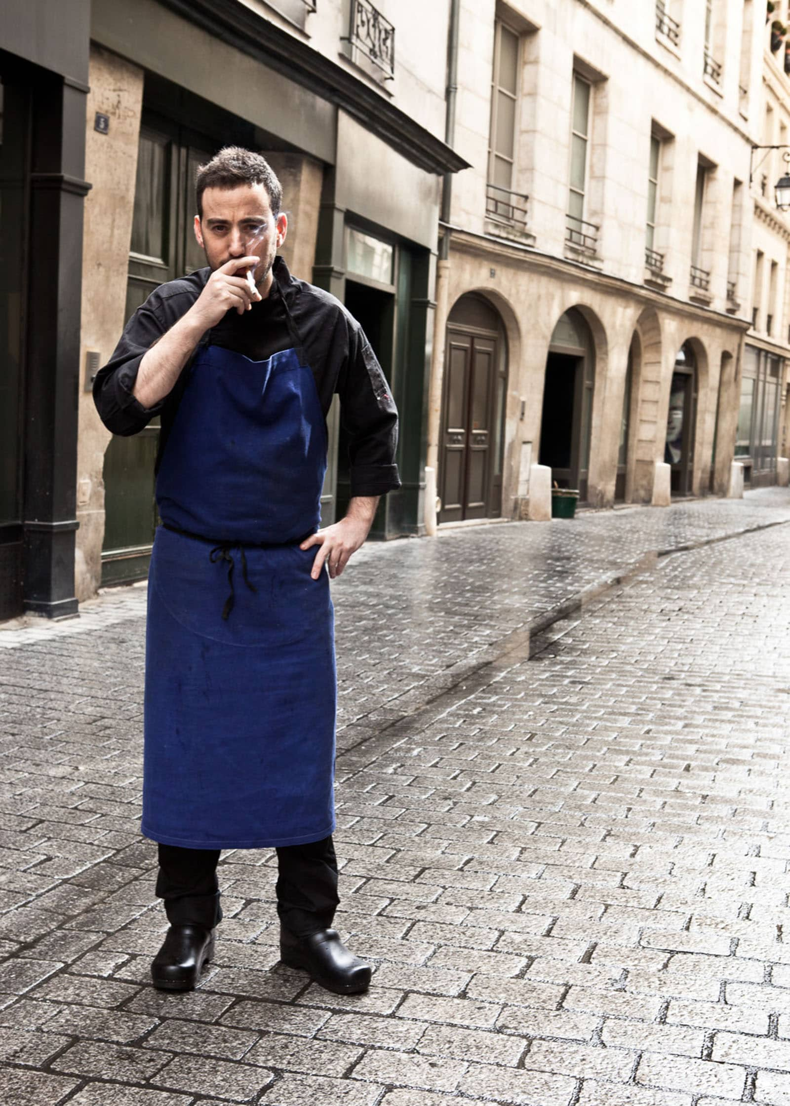 On the streets of Paris with Chef Daniel Rose in his kitchen apron having a cigarette.