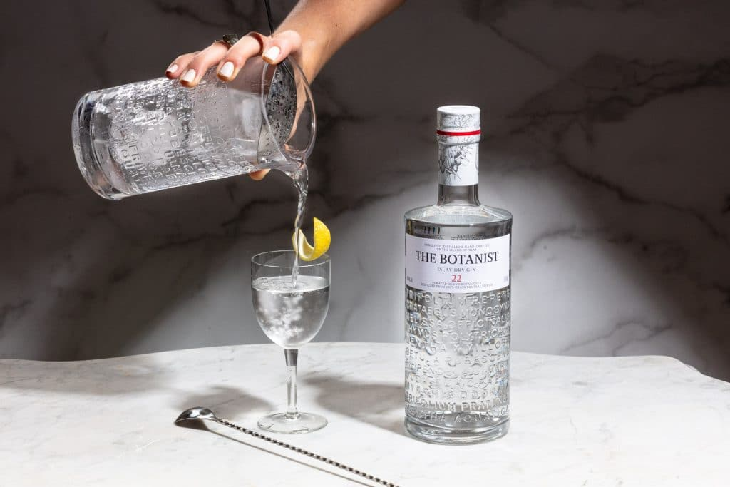 This action shot of a Martini being poured from a mixing glass is set next to a bottle of Botanist Gin.