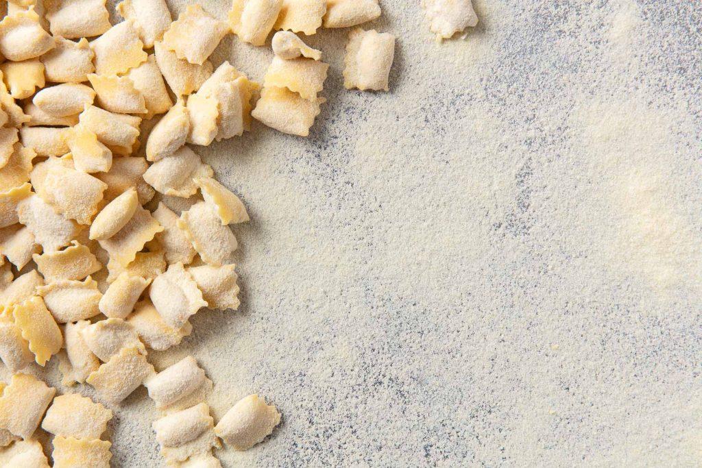 Product photograph of some handmade Agnolotti pasta on cornmealed surface.