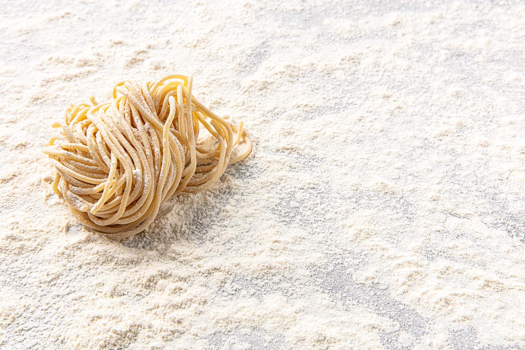 Product details of some handmade Spaghetti pasta on floured surface.