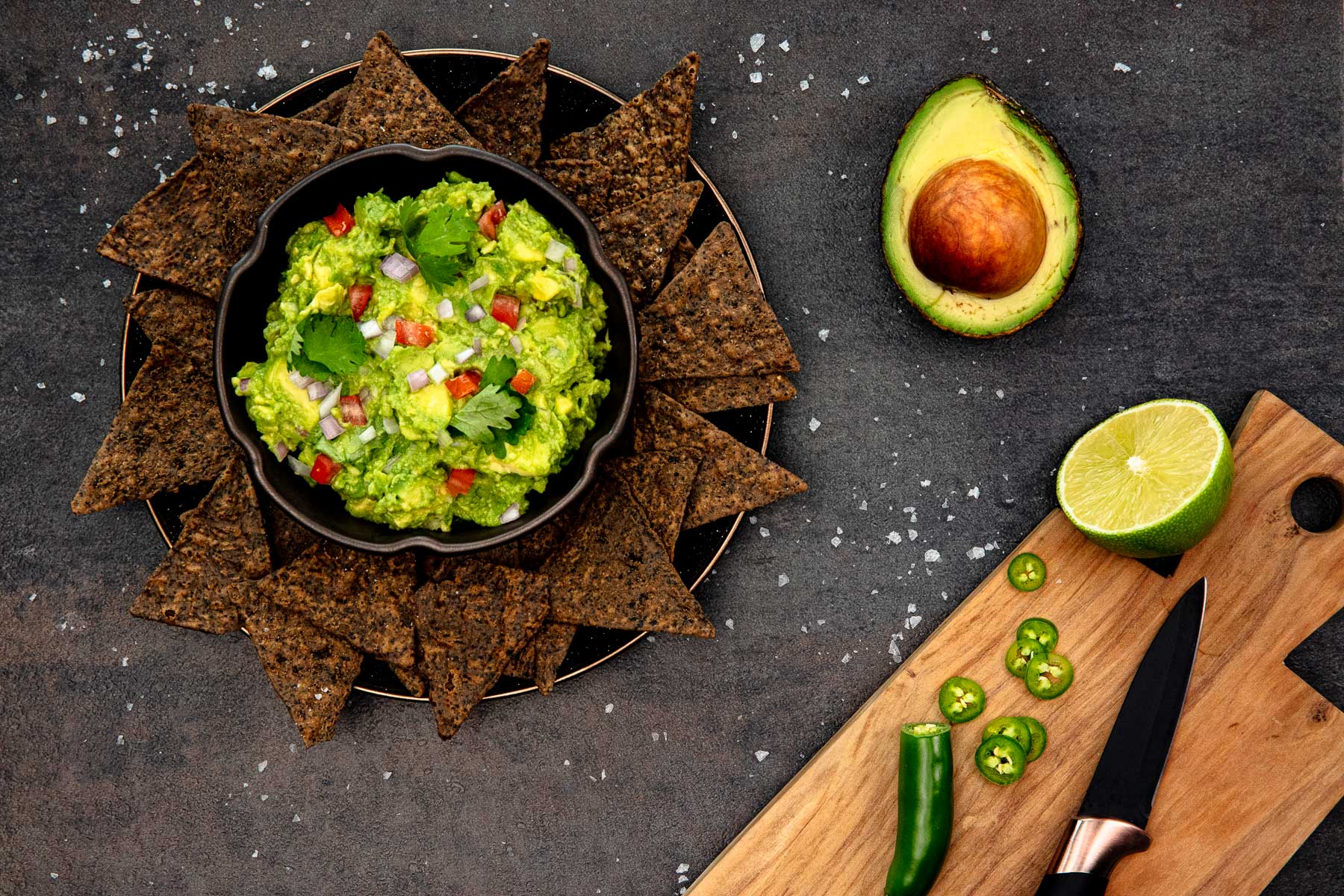 A bowl of guacamole sits amidst a bed of triangular dark brown hemp chips alongside a half an avocado, half a lime and a jalapeno.