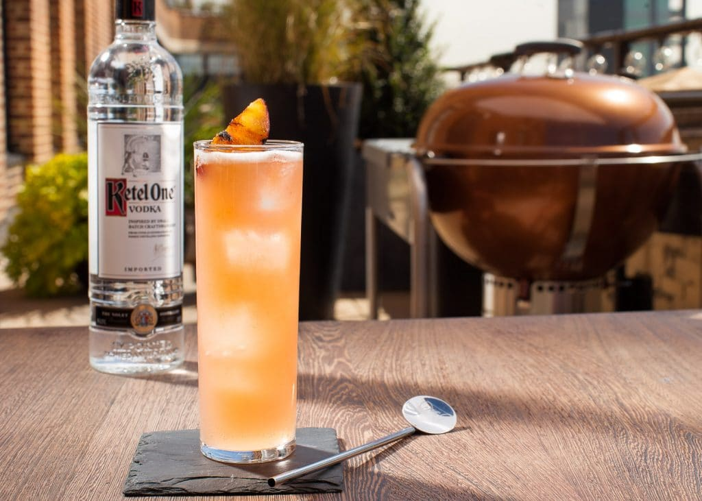 A pale orange liquid in a high ball glass with a bottle of Ketel One Vodka on a table with a copper colored charcoal grill in the background.