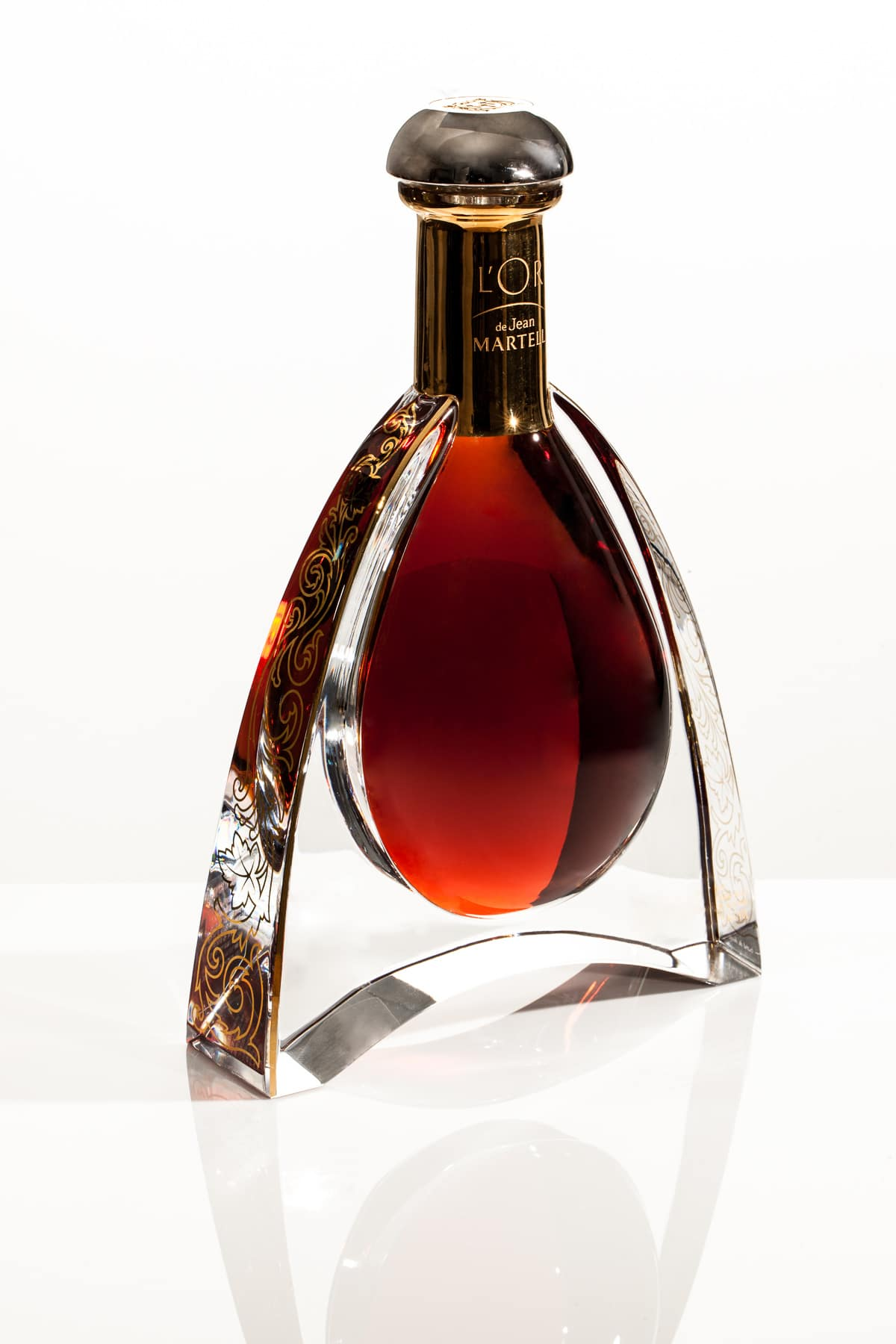 Bottle photography of L'or Martell Cognac on a white background is photographed at a low angle.