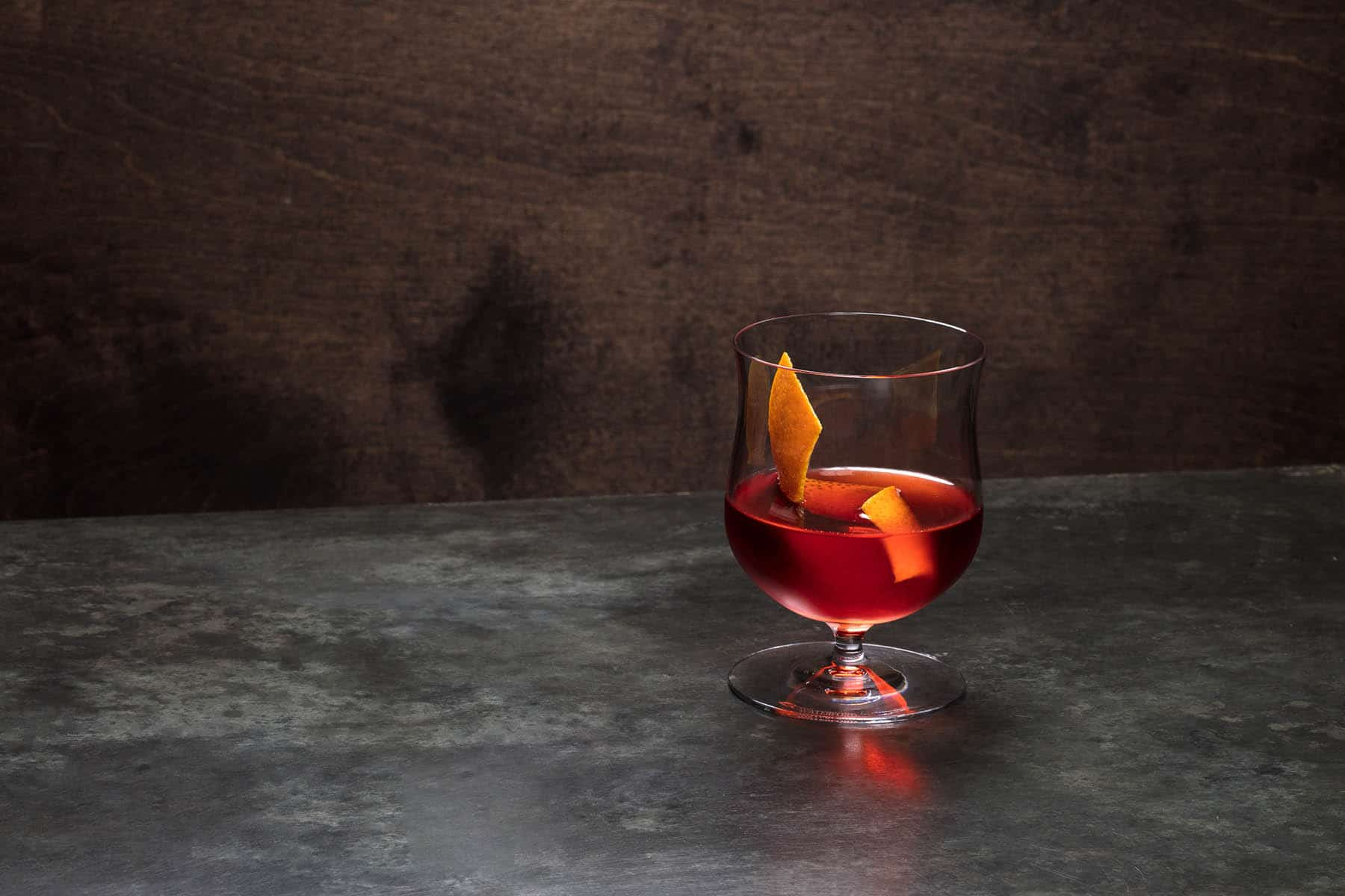 Seen here is an aged rum negroni served in a snifter glass with an orange peel.