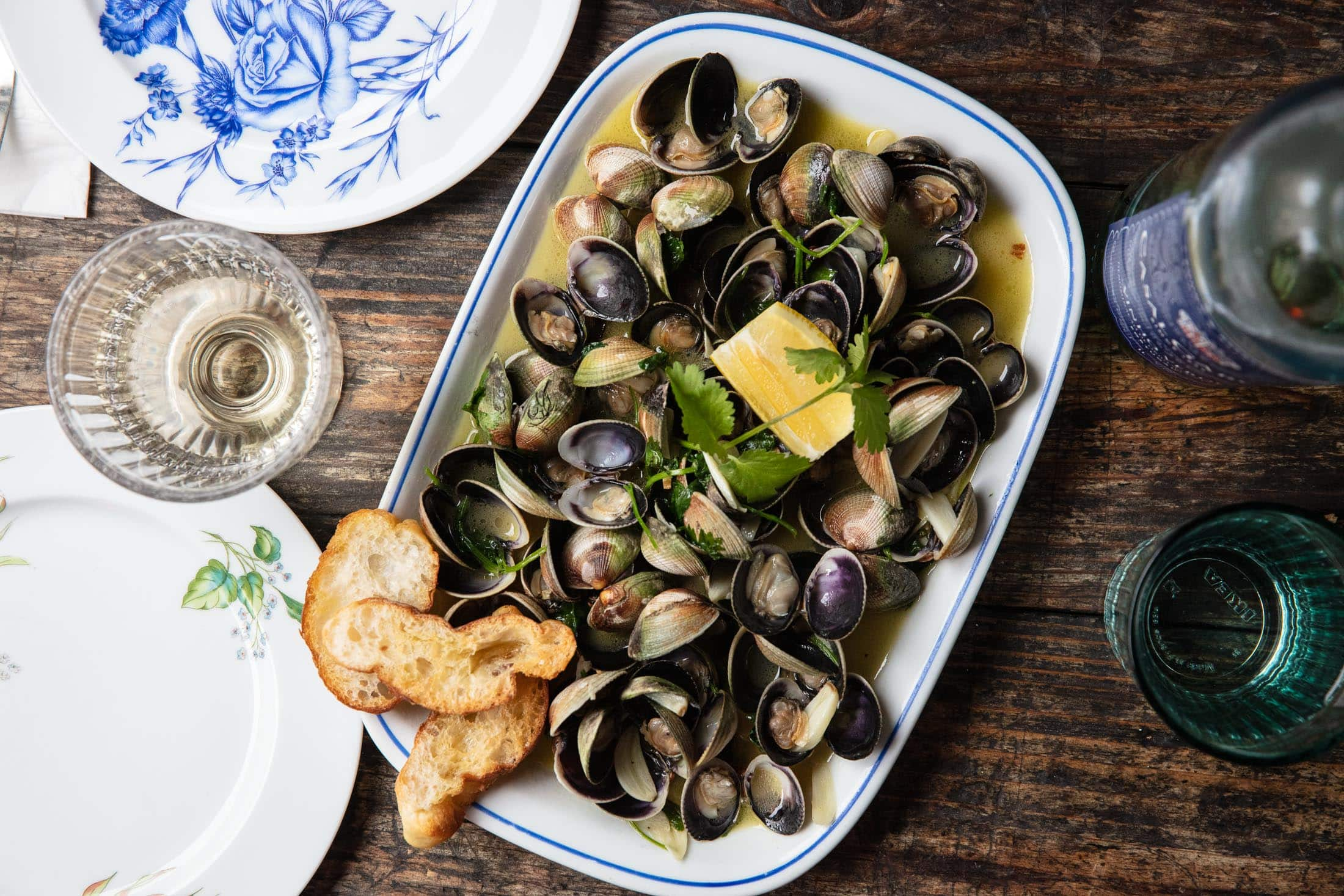 Top down food photograph of clams in a butter garlic sauce sits on a rustic wood table scape. Also known as À Bulhão Pato.