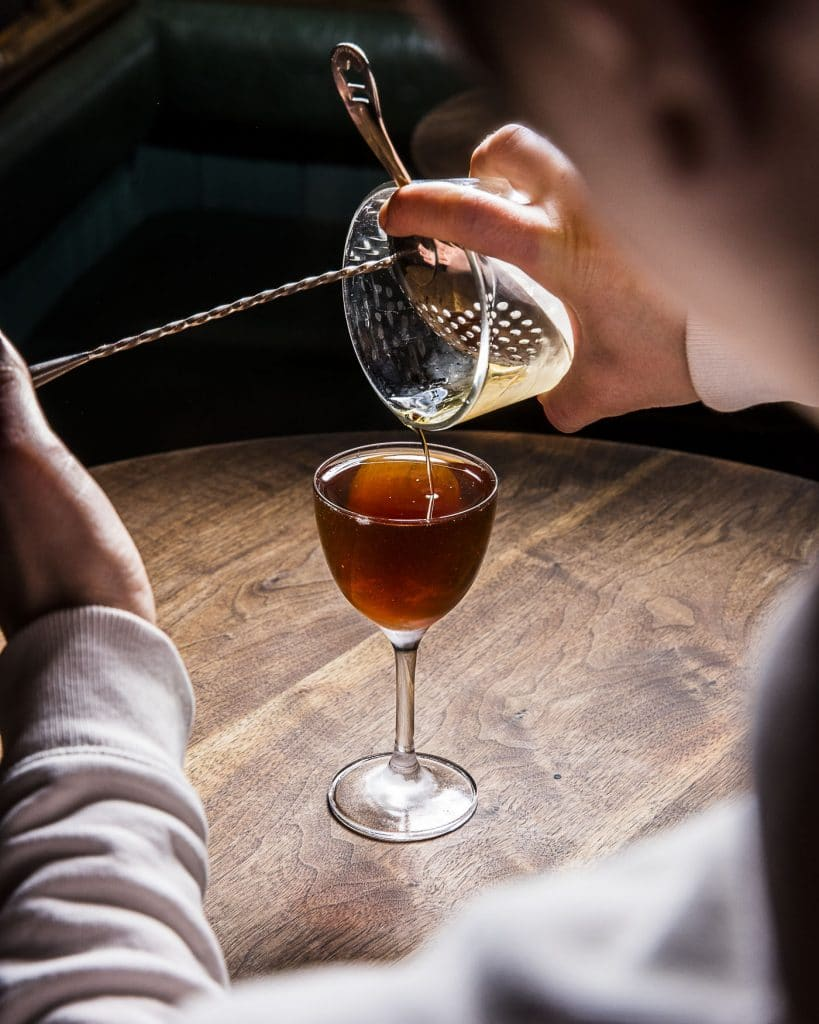 From the mixing glass, Mixologist Jillian Vose, pours the last drops of a Manhattan cocktail.