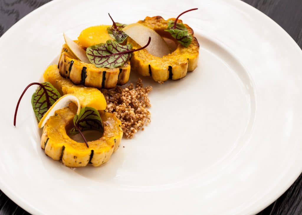Atop a white plate sits a bed of couscous with roasted yellow acorn squash garnished with sorrel leaves and pear slices.