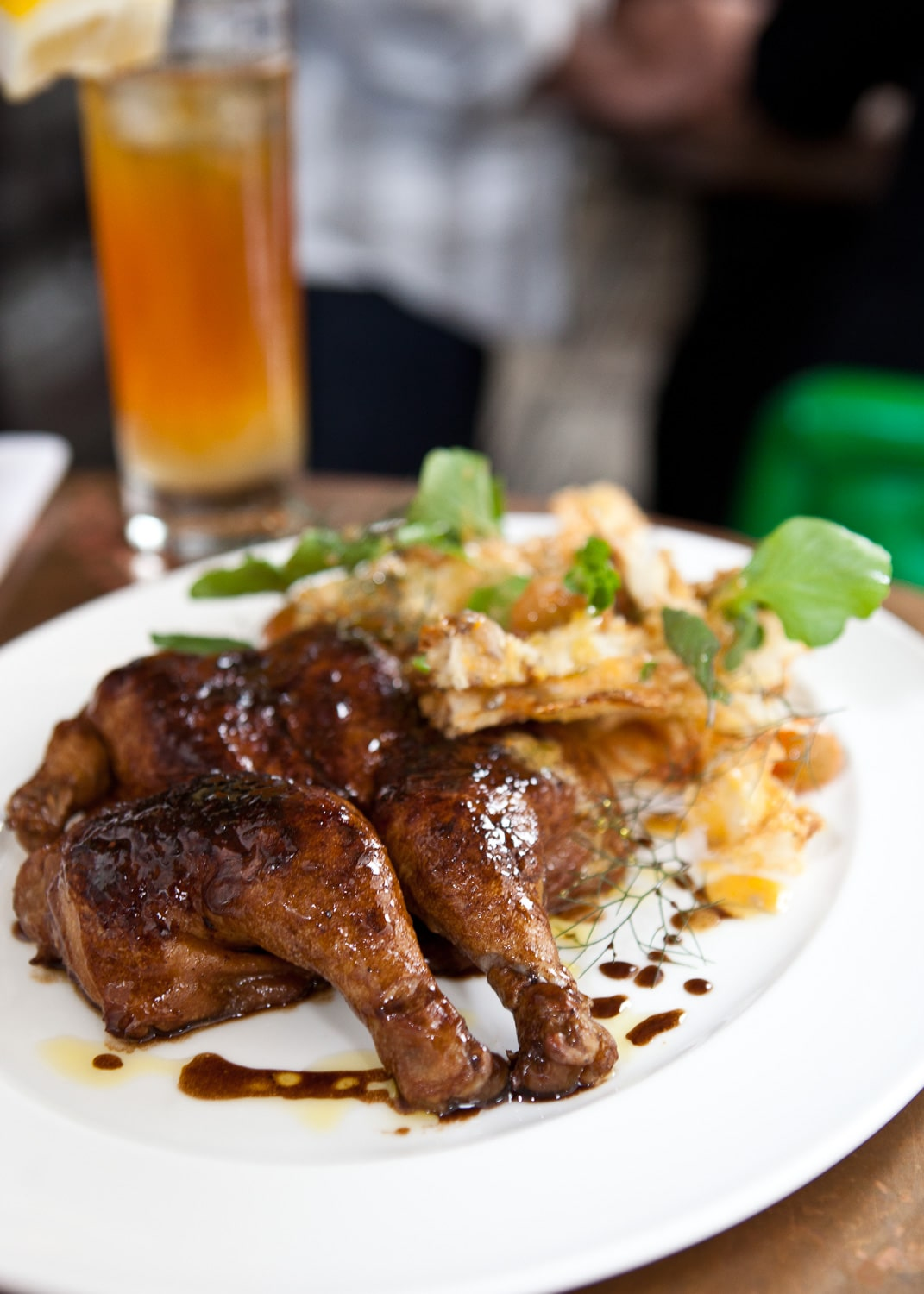 This food photo of a roasted cornish hen is served on a white plate with potato chips and a cocktail in the background.