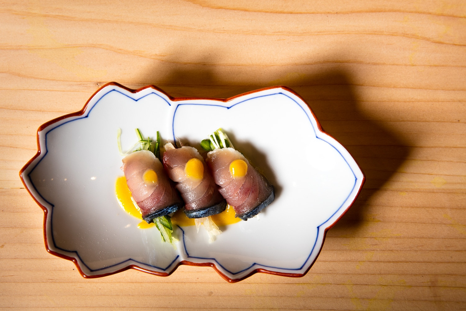 A thinly sliced piece of sashimi wraps cucumbers with a spicy aioli sauce on it. The ornamental shaped plate casts a hard shadow onto the natural pine wood.