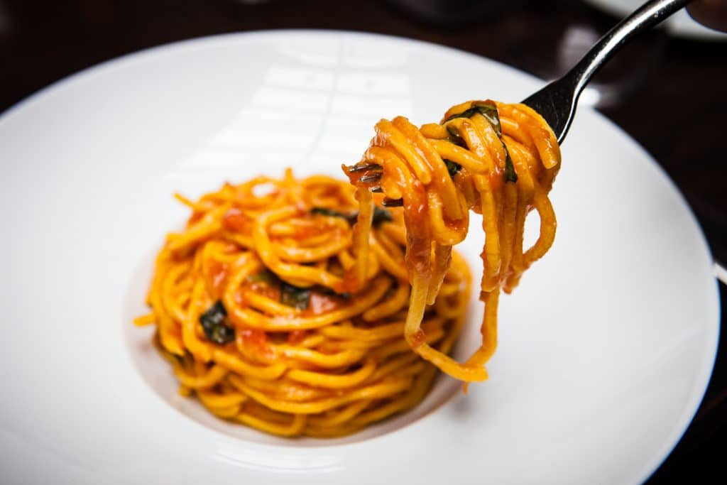 Noodles from a nest of spaghetti dressed with red sauce in a white bowl wind around a silver fork.