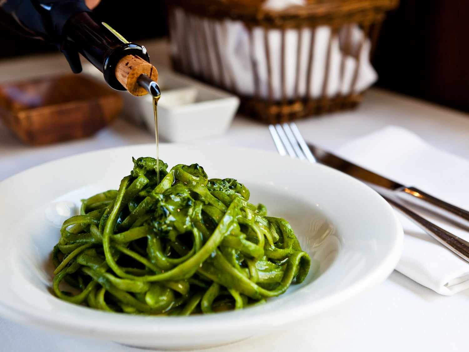 Olive oil is drizzled over a tangle of linguine coated in bright green sauce in a white bowl at a set table.