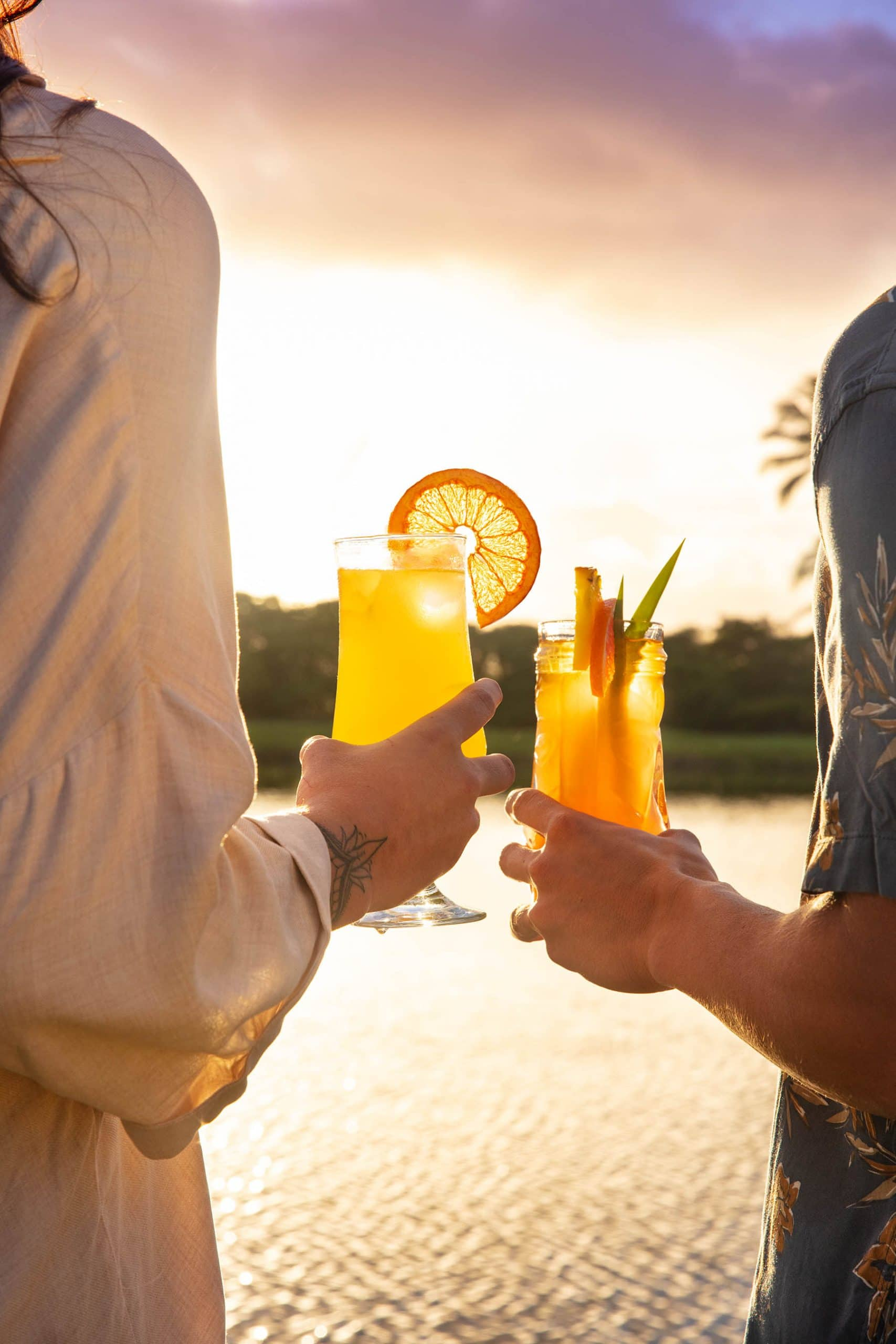A lifestyle image of a couple holding two cocktails watching the sunset in Hawaii.