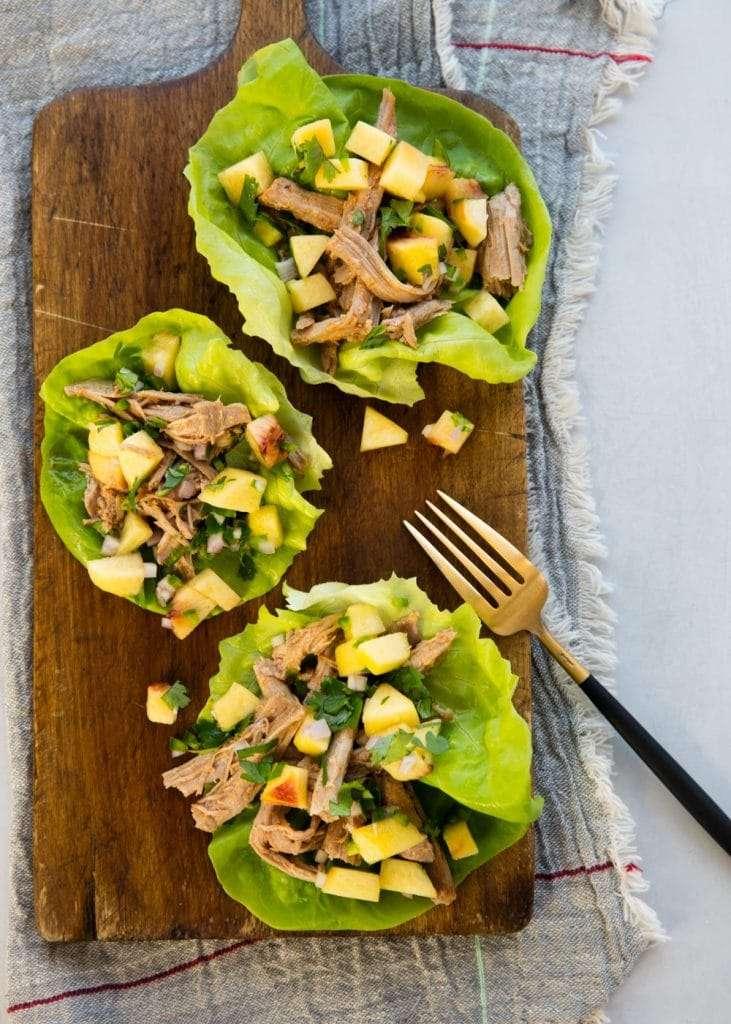 Fresh Bibb lettuce cups on a rustic cutting board containing shredded pork and mango salsa