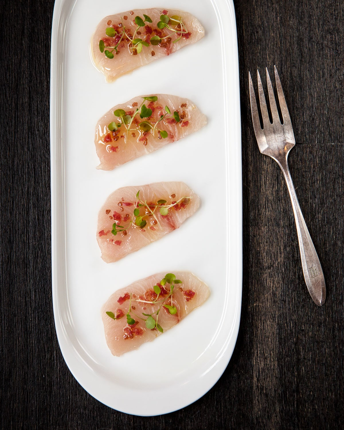Four slices of fresh yellowtail fish topped with a raw salsa of chilies and oil on a white oval platter.