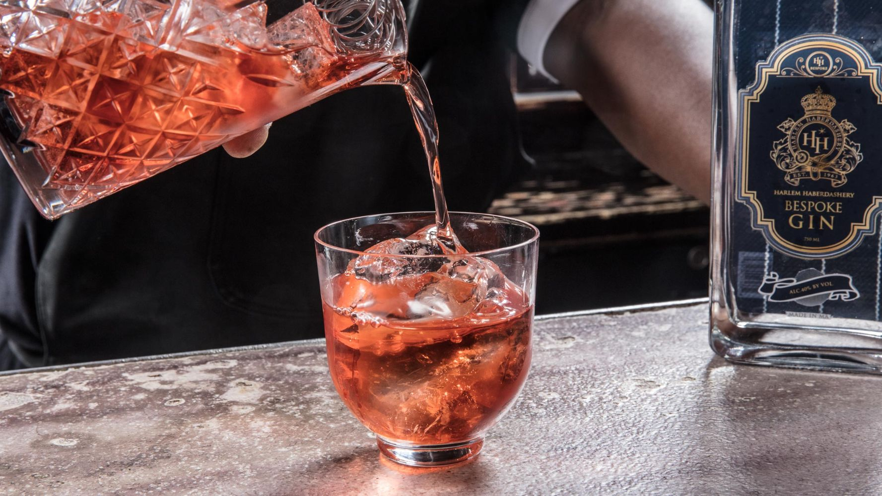 Close-up of a bartender pouring a negroni cocktail from a mixing glass into a rocks glass next to a bottle of HH Bespoke Gin.