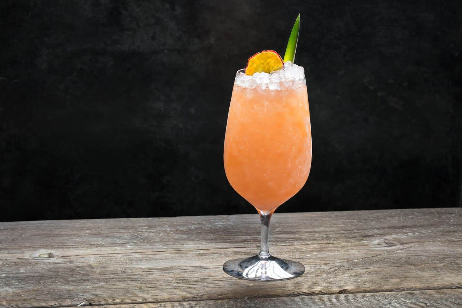 This orange colored passion fruit pineapple hurricane is served over crushed ice.
