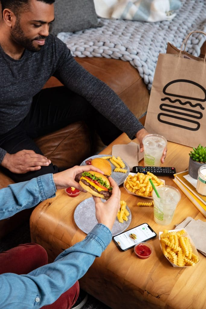 Seen in this lifestyle photograph is a couple at home eating burgers and fries from Shake Shack.