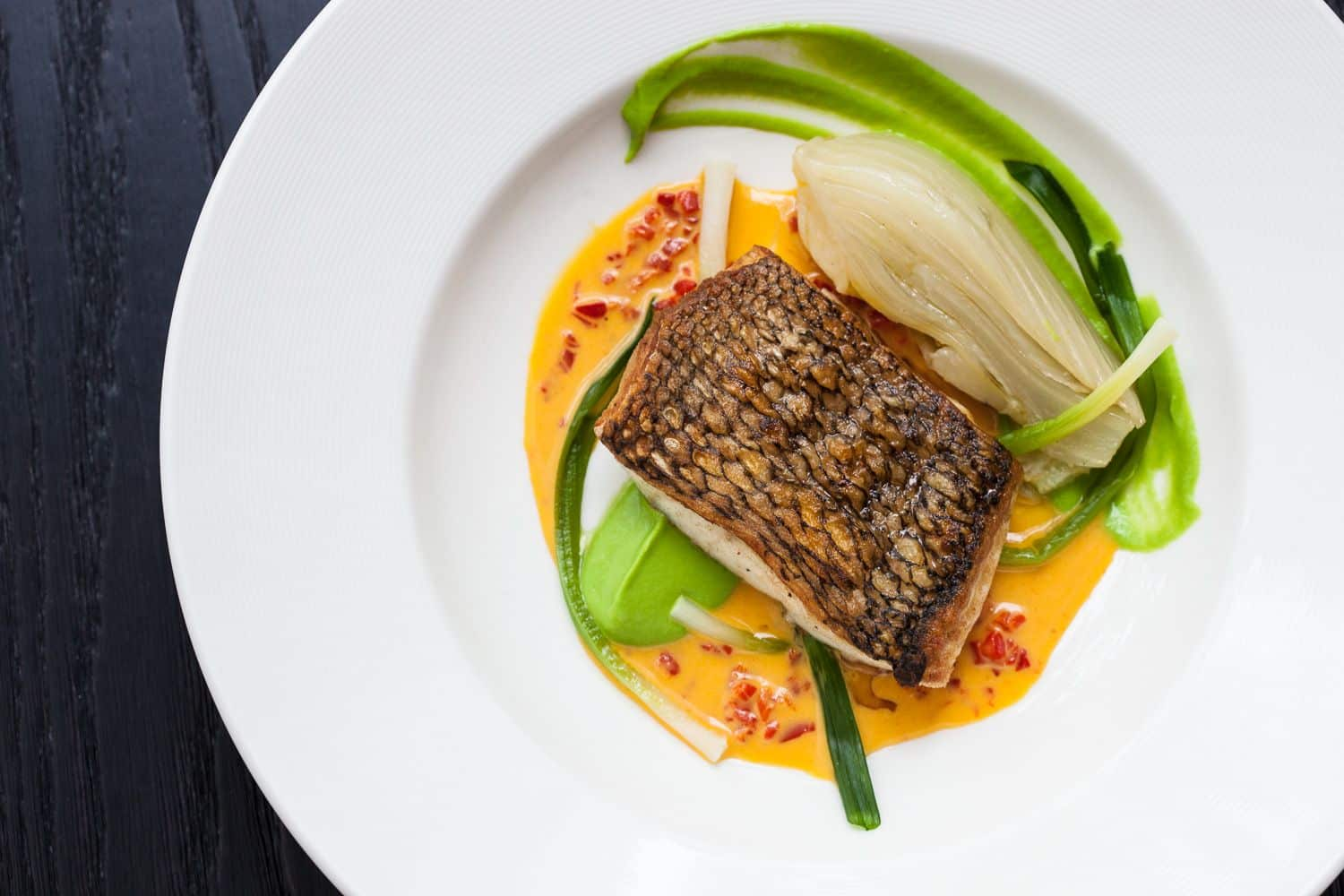 Looking top down at this Atlantic Bass fish dish is contrasted with green onion, roasted artichoke, and a carrot pepper reduction.