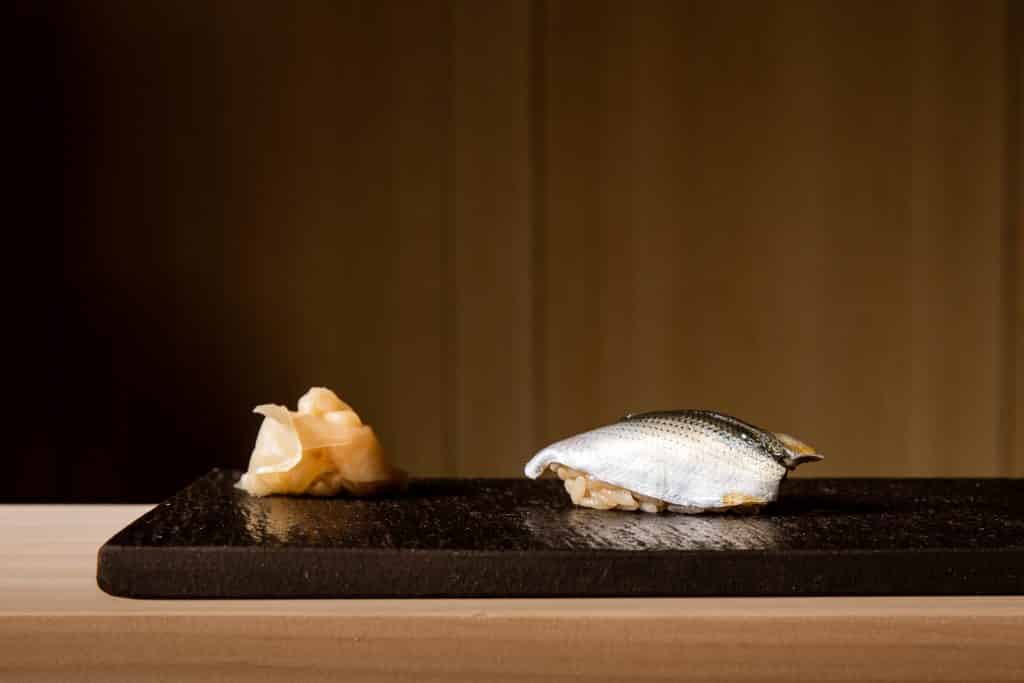 This food photograph of nigiri with a side of ginger is plated on a black slate.