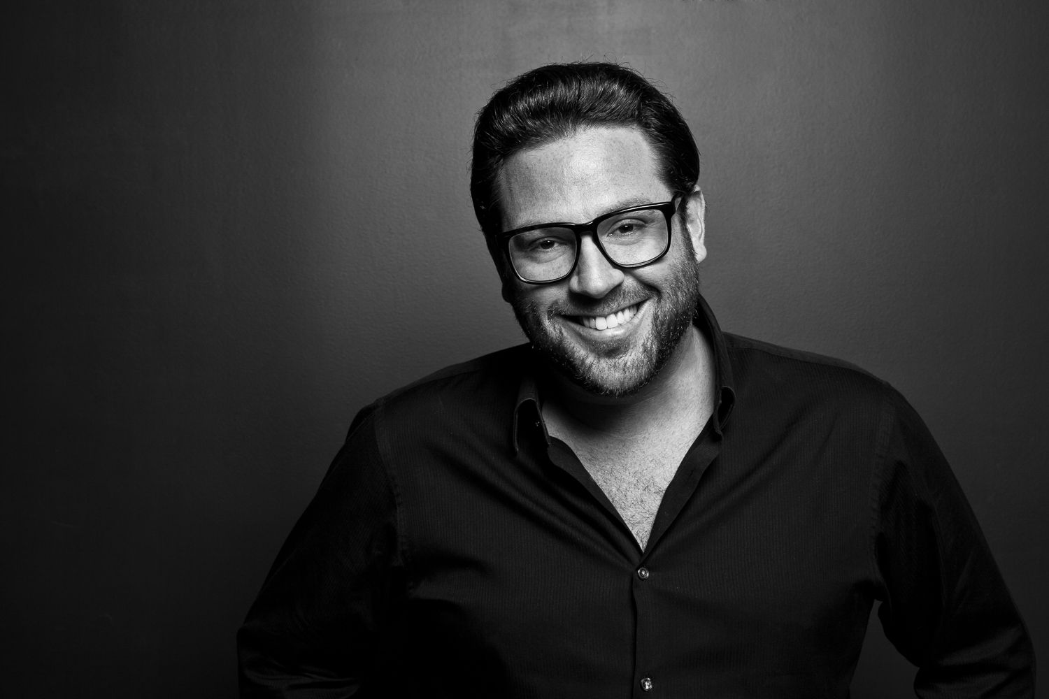 Chef Scott Conant smiles in a black and white photographer.
