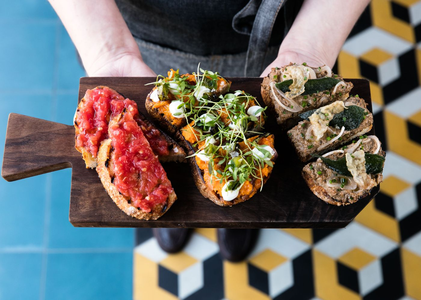 Three types of Danish-style Smørrebrød presented on a wooden platter against colorful blue, yellow, black and white tiles.