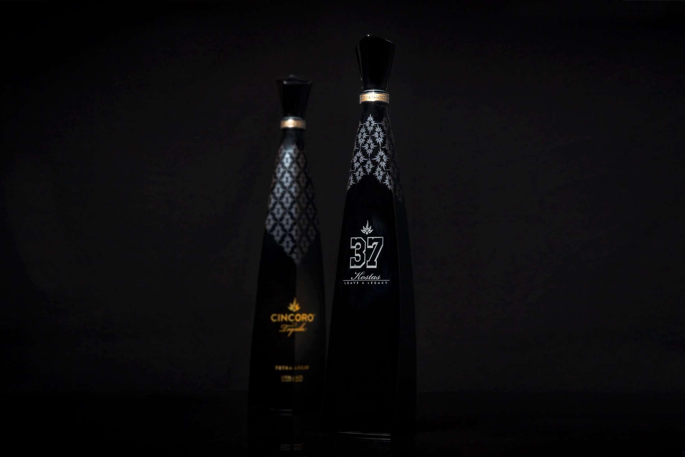 Bottle Photography for Cincoro Tequila shot on black of engraved bottles.
